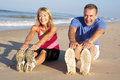 Senior Couple Exercising On Beach Stock Photo
