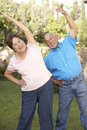 Senior Couple Exercising In Garden Royalty Free Stock Photo