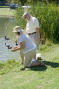 Senior Couple Feeding Ducks At Pond Royalty Free Stock Photo