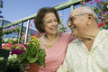 Senior couple among flowers at plant nursery closeup of a smiling the Stock Images