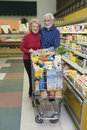 Senior couple food shopping in supermarket portrait of a smiling Stock Photography
