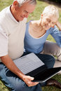 Senior couple in garden with laptop Royalty Free Stock Photo