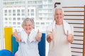 Senior couple gesturing thumbs up in gym portrait of happy Stock Images