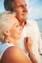 Senior couple getting married in beach ceremony looking out to sea Royalty Free Stock Images