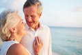 Senior couple getting married in beach ceremony looking out to sea Stock Photos