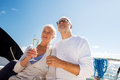 Senior couple with glasses on sail boat or yacht sailing age travel holidays and people concept happy champagne deck floating in Stock Images