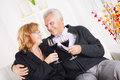 Senior couple happy sitting embraced at home smiling and drinking red wine Stock Images
