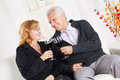 Senior couple happy sitting together at home smiling and drinking red wine Stock Photo