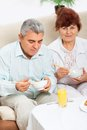Senior couple having breakfast smile fruit orange juice sitting at table home kitchen Royalty Free Stock Images