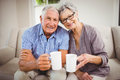 Senior couple having coffee in living room portrait of sitting on sofa and Stock Photos