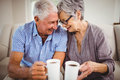 Senior couple having coffee in living room sitting on sofa and Stock Photography