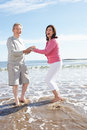 Senior couple having fun on beach holiday smiling to camera Royalty Free Stock Photography