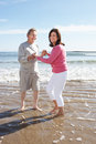 Senior couple having fun on beach holiday smiling to camera Stock Image