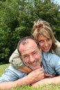 Senior couple having fun outdoors lying in grass laying Royalty Free Stock Photography