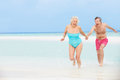 Senior couple having fun in sea on beach holiday smiling Royalty Free Stock Photos