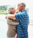 Senior couple having fun by a swimming pool Stock Photo
