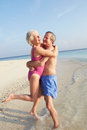 Senior couple having fun on tropical beach holiday portrait of smiling to camera Royalty Free Stock Photos