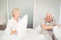 Senior couple having pillow fight in bed Royalty Free Stock Photo