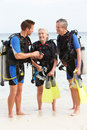 Senior couple having scuba diving lesson with instructor smiling to each other Royalty Free Stock Photo