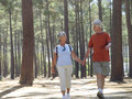 Senior couple hiking in wood holding hands side by side smiling front view Royalty Free Stock Image