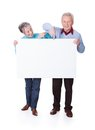 Senior couple holding blank placard happy on white background Royalty Free Stock Images