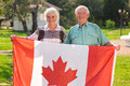 Senior couple holding Canadian flag. Royalty Free Stock Photo