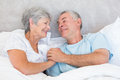 Senior couple holding hands in bed romantic at home Royalty Free Stock Photos