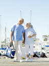 Senior couple holding hands on jetty smiling at each other low angle view Stock Image