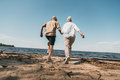 Senior couple holding hands and running on sandy beach Royalty Free Stock Photo