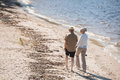 Senior couple holding hands and walking on sand at riverside Royalty Free Stock Photo