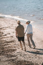 Senior couple holding hands and walking on sandy beach Royalty Free Stock Photo