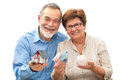 Senior couple holding a house model and piggy bank attractive Stock Photos