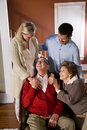 Senior couple at home on sofa with adult children Stock Photos