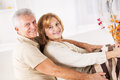 Senior couple hugging sitting in living room Stock Photography