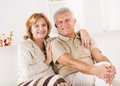 Senior couple hugging sitting in living room Stock Images