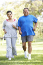 Senior Couple Jogging In Park Stock Image