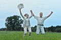 Senior couple jumping in summer field beautiful Royalty Free Stock Images