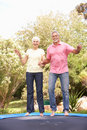 Senior Couple Jumping On Trampoline In Garden Stock Photo