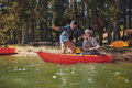 Senior couple on kayak in the lake portrait of mature men with a women a men showing something interesting to women holding Royalty Free Stock Photography