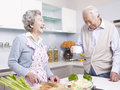 Senior couple in kitchen asian talking and laughing Stock Images