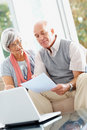 Senior couple with laptop reading a document Royalty Free Stock Photo