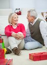 Senior couple looking at each other happy while sitting on floor during christmas Royalty Free Stock Photos