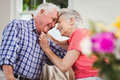 Senior couple looking at each other and smiling in living room Royalty Free Stock Photo