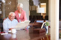 Senior couple looking at photo album through window wearing glasses smiling Stock Photos