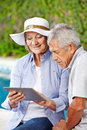 Senior couple looking at tablet computer outdoors pool Royalty Free Stock Image
