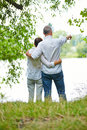Senior couple looking together into the future standing on a lake and Royalty Free Stock Image