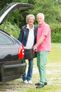 Senior couple with luggage at a black car Stock Image