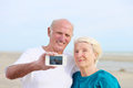 Senior couple making self photo on the beach happy loving enjoying vacation together having fun taking selfie using smartphone Stock Photo