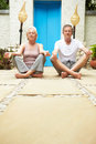 Senior couple meditating outdoors at health spa facing camera Stock Photography