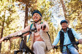 Senior couple mountain biking on a forest trail, low angle Royalty Free Stock Photo